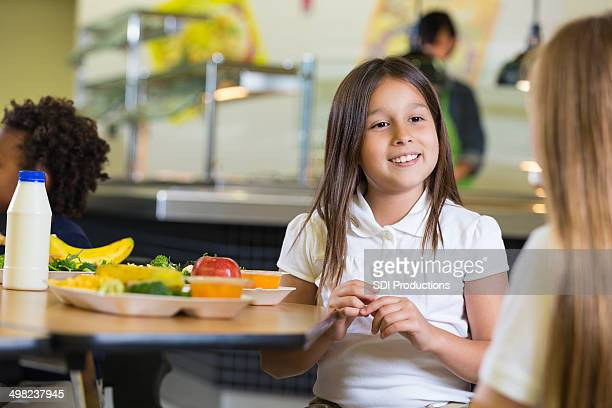 Private elementary school girls eating healthy food in cafeteria lunchroom