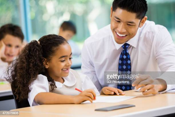 Private elementary school teacher teaching young student