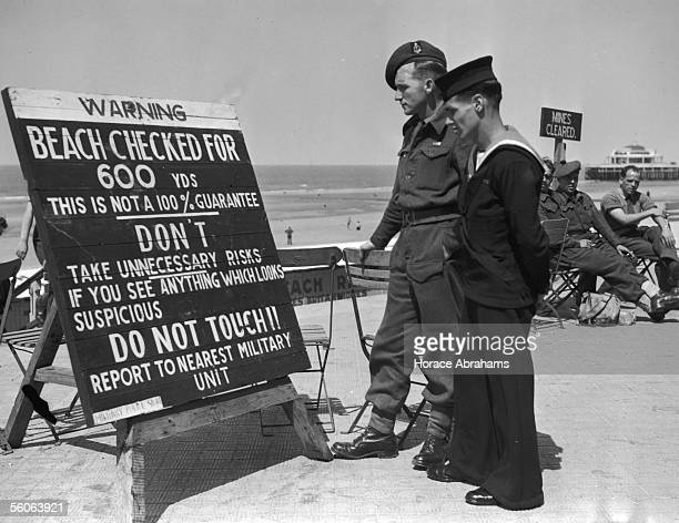 Private Ernest Fellows and navy telephonist Arthur Beadsley read a sign on a Belgian beach at the end of World War II July 1945 The sign warns that...