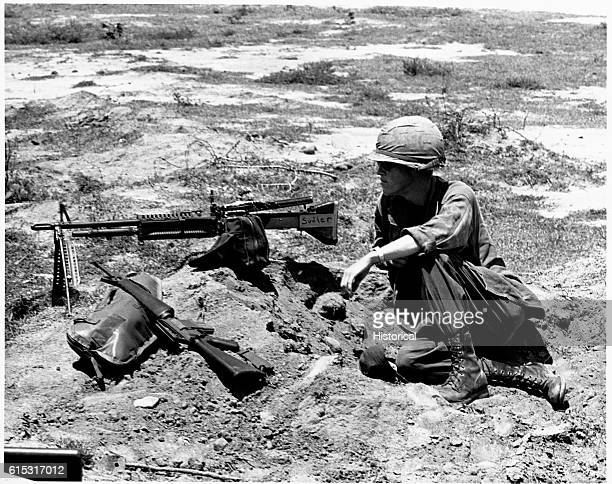 Private First Class John Lakey with M60 machine gun and M16 rifle keeps a watch for possible Vietcong as other members of his company 'dig in'
