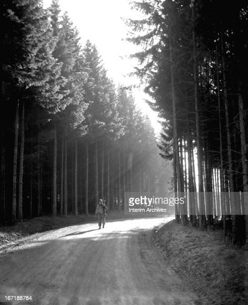 Private First Class Margerum returns from the front lines and walks through a quiet section of a forest near Bastogne, possibly Belgium or...