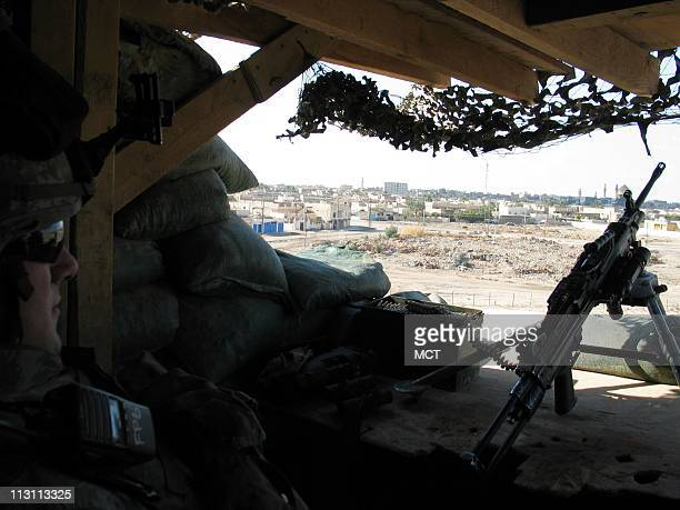 Private First Class Troy Fisher of Bloomington Indiana sits at an observation post earlier this month on top of the schoolhouse where he and his...