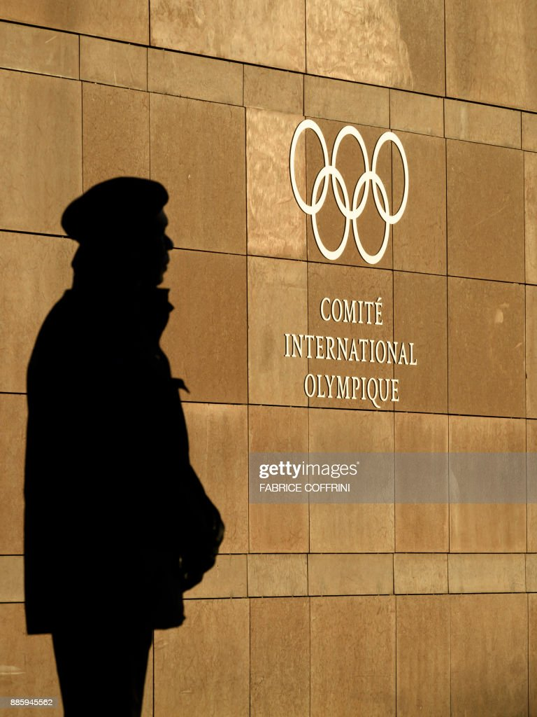 A private guards is seen in silhouette in front of the International Olympic Committee (IOC) at their headquarters prior to an executive meeting on December 5, 2017 in Pully near Lausanne. The International Olympic Committee meets to decide whether to bar Russia from the 2018 Winter Olympics for doping violations, in one of the weightiest decisions ever faced by the Olympic movement. / AFP PHOTO / Fabrice COFFRINI