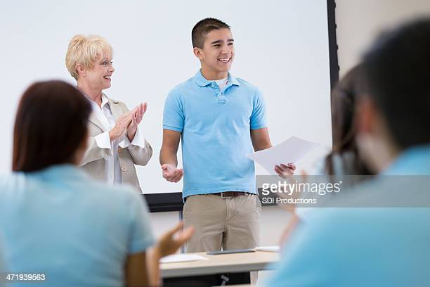 Private high school student giving speech in front of classroom