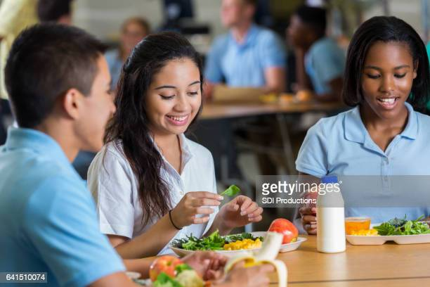 Private high school students eat a healthy lunch in cafeteria