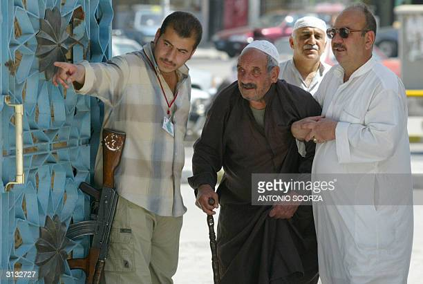 A private Iraqi security guard shows the way to an old man at the entrance of Baghdad's Sunni Muslim Aazamiya Mosque at the start of the weekly...