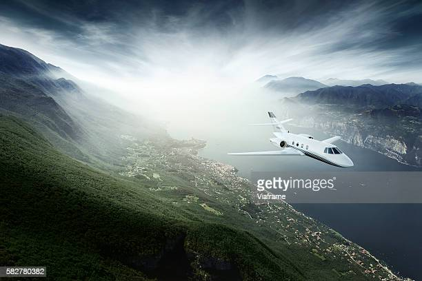 Private jet flying above lake