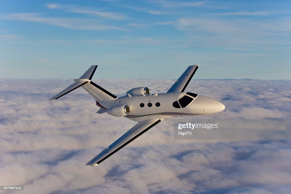 A Private Jet Flying Above The Clouds Onroute To Its
