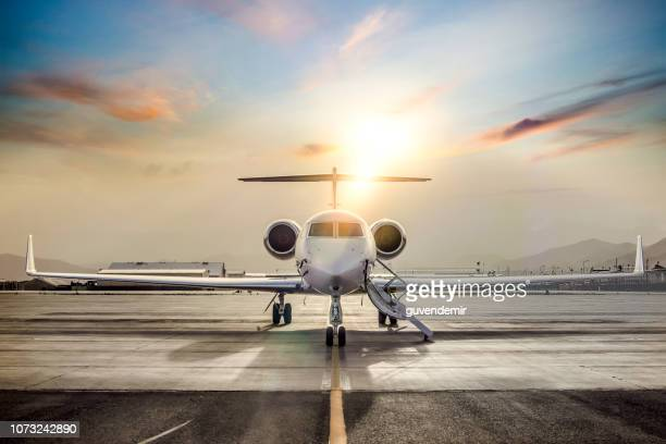 private jet on airport runway - aeroplane stock photos and pictures