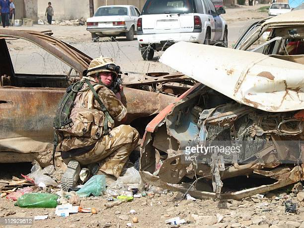 Private Joey Ford pulls guard outside of an Iraqi police station in Amarah as his fellow British soldiers move toward their armored vehicles Shiite...