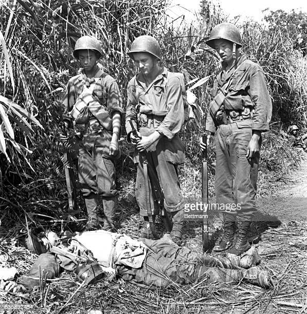Private John Gavenas of Shenandoah PA with two ChineseAmerican members of General Merrill's infantrymen look at the body of slain Japanese These men...