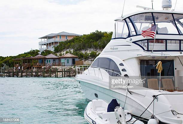 Private luxury yacht with dinghy and US-ensign on June 15, 2012 in Staniel Cay Marina, The Bahamas.