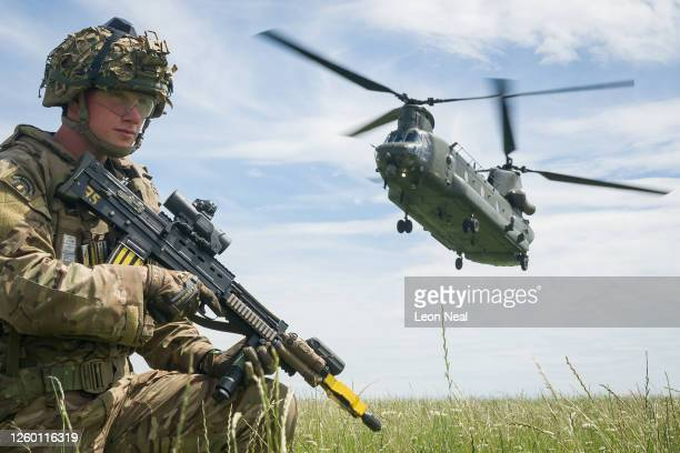 Private Patrick Rodgers of the Anglian Regiment, 2nd Battalion maintains the perimeter as a Chinook helicopter arrives for a medical evacuation...