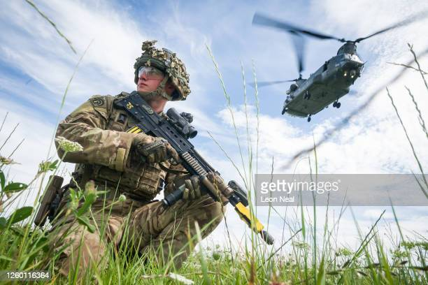 Private Patrick Rodgers of the Anglian Regiment, 2nd Battalion maintains the perimeter as a Chinook helicopter carries out a medical evacuation...