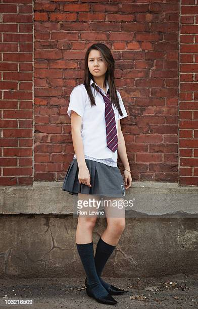 Private school girl standing against a brick wall
