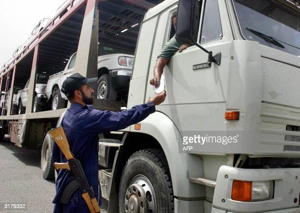 A private security agent checks the papers of a truck loaded with Japaneses cars leaving Umm Qasr's port 80 Km from Basra 31 March 2004 in southern...