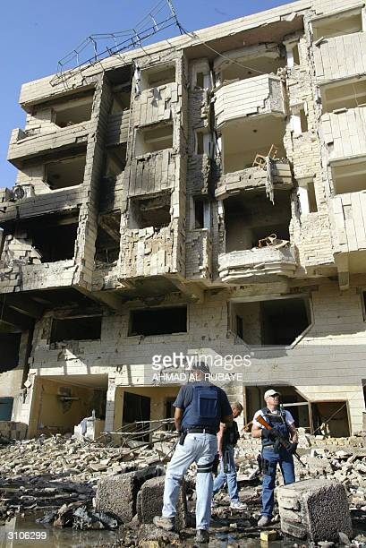 Private security contractors stand in front of the devastated Jabal Lubnan hotel 18 March 2004 at the site of last night's powerful car bomb...