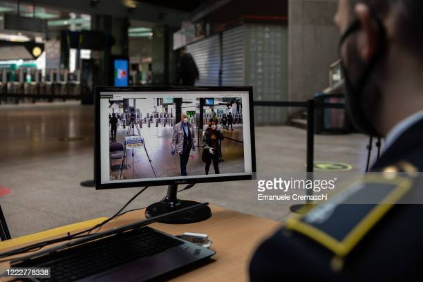 A private security guard controls a monitor connected to a thermo scanner revealing body temperature as passengers arrive at Cadorna railway station...