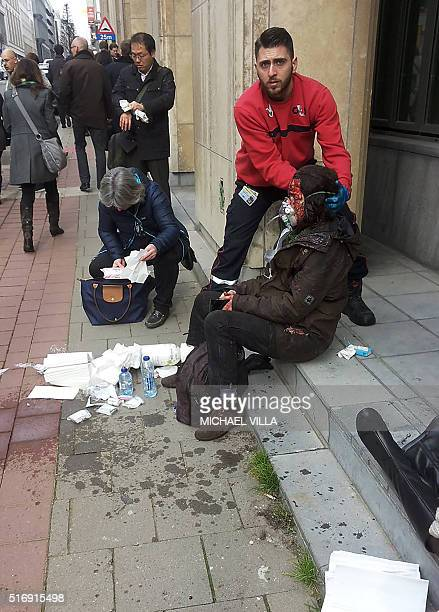 A private security guard helps a wounded women outside the Maalbeek Maelbeek metro station in Brussels on March 22 2016 after a blast at this station...