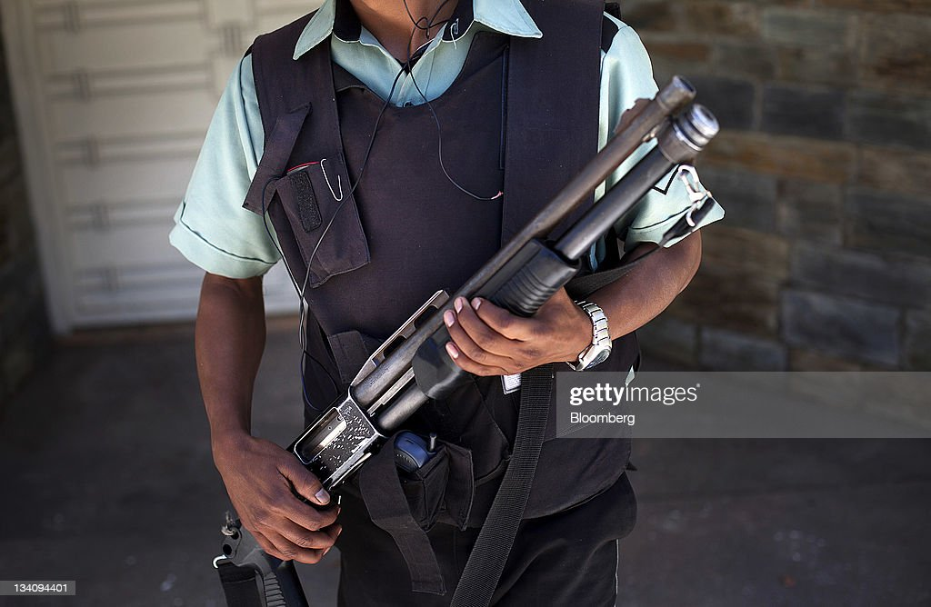 A private security guard holds a gun while standing for a photograph in Guatemala City, Guatemala, on Wednesday, Nov. 23, 2011. Foreign direct investment in Guatemala will stagnate this year at about $668 million, after rising 22 percent in 2010, according to the International Monetary Fund (IMF). Photographer: Victor J. Blue/Bloomberg via Getty Images
