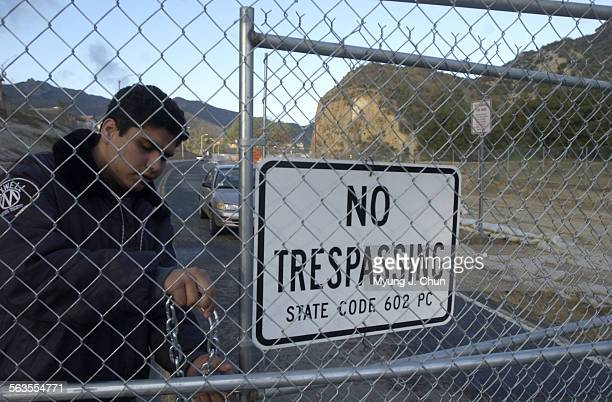 A private security guard locks up a newly installed gate on Pico Canyon Road in Stevenson Ranch The private property line was extended well beyond...