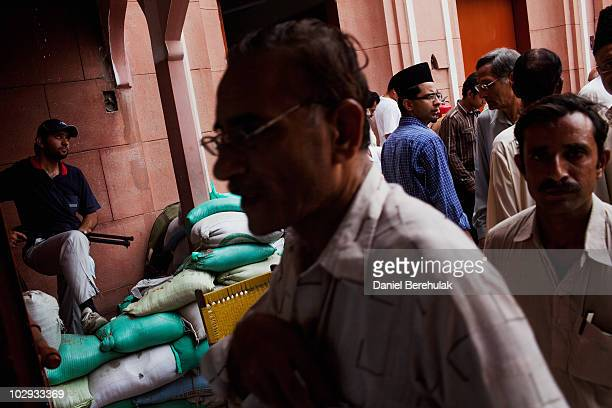 A private security guard looks on as members of the persecuted Ahmadiyya community gather for Friday prayers at the Garhi Shahu mosque on July 16...