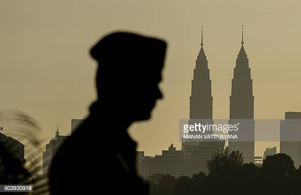 A private security guard walks past as the sun rises over Malaysia's iconic Twin towers in Kuala Lumpur on January 8 2016 AFP PHOTO / MANAN...