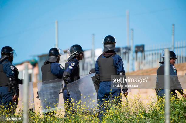 Private security guards keep an eye as people lay out plots and build shacks on a piece of land belonging to the Louiesenhof Wine Estate on August 8...