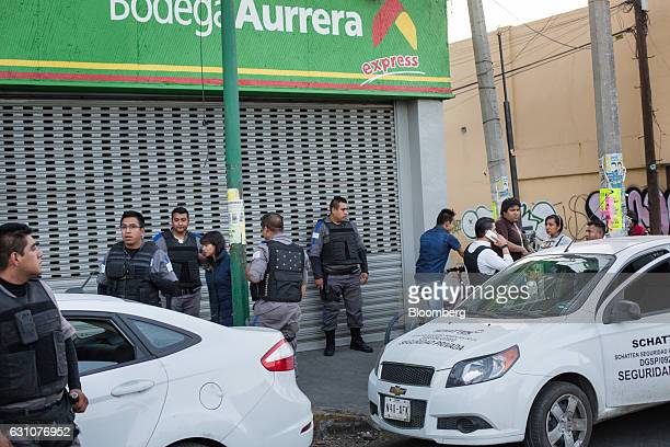 Private security guards stand outside a store following looting and protests over the gasoline price hike in Mexico City Mexico on Thursday Jan 5...