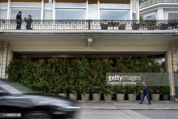 Private security guards stands at the entrance of The Fairmont Le Montreux Palace hotel hidden by plants in Montreux on May 29 which is scheduled to...