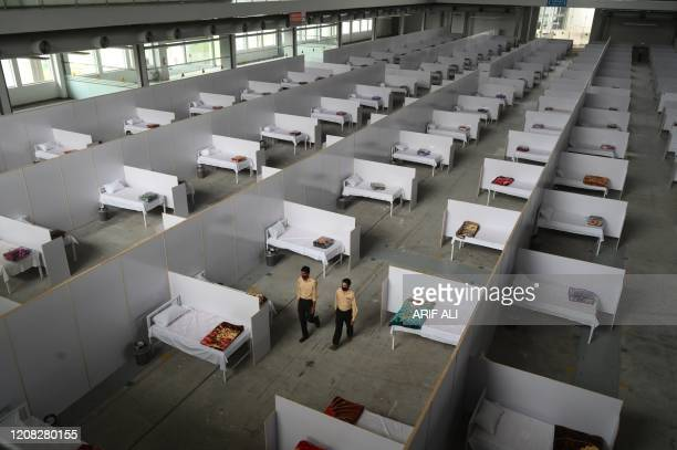 Private security guards walk along a temporary isolation facility set up at the Expo Center during a government-imposed nationwide lockdown as a...