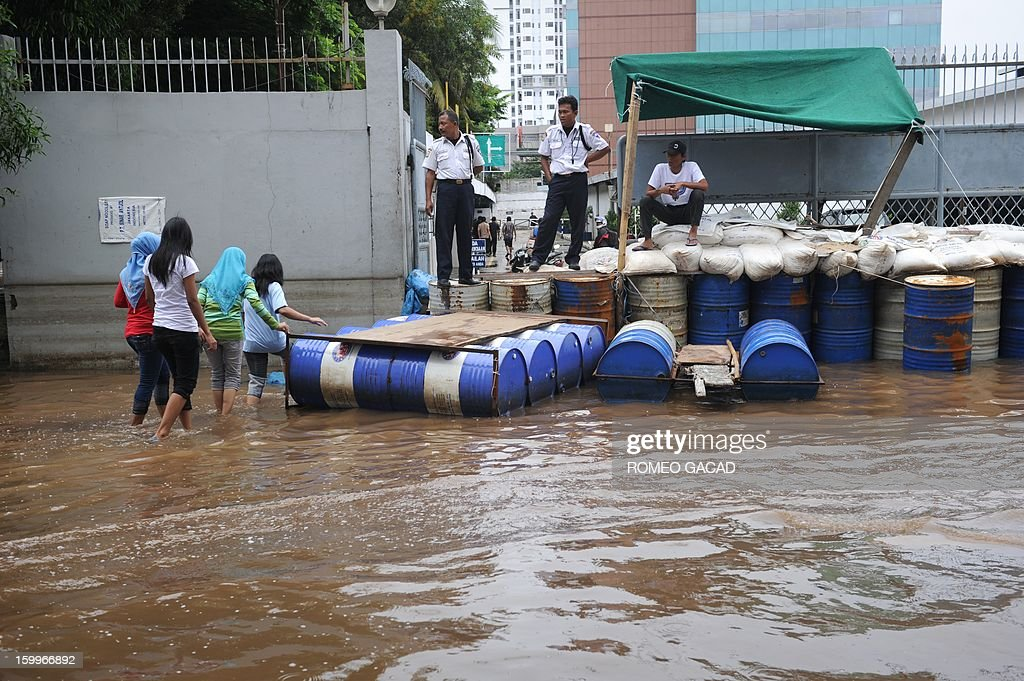 Private security personnel man sand bags to protect a factory compound from flood waters in a flooded neighborhood in Jakarta on January 24, 2013. Indonesia's National Disaster Mitigation Agency (BNPB) said more than 30,000 people were displaced while 20 people died during the widespread flooding that hit Jakarta as the weather bureau forecast more rains in the coming days.
