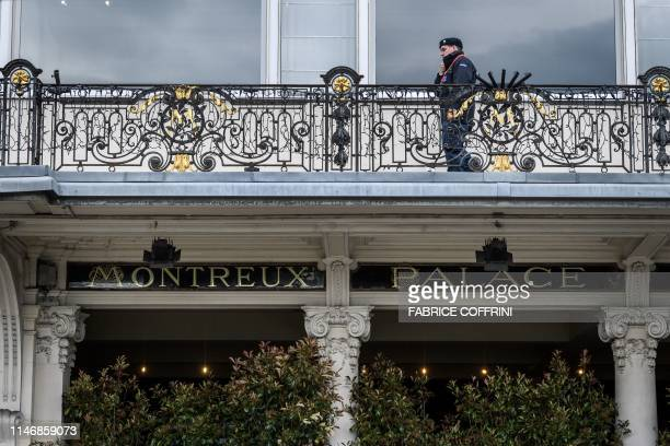 A private secury guard is seen above the entrance of The Fairmont Le Montreux Palace hotel in Montreux on May 29 which is scheduled to host the...