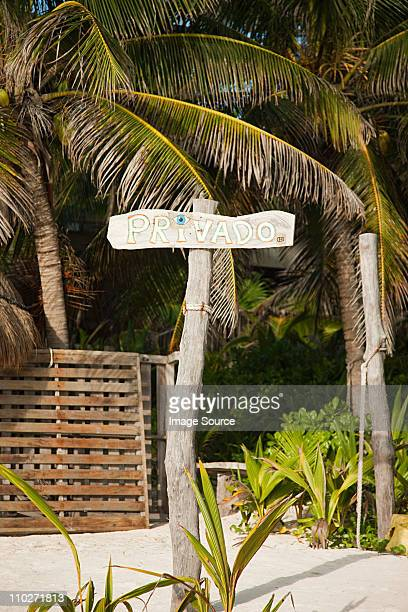 Private sign and palm trees on beach