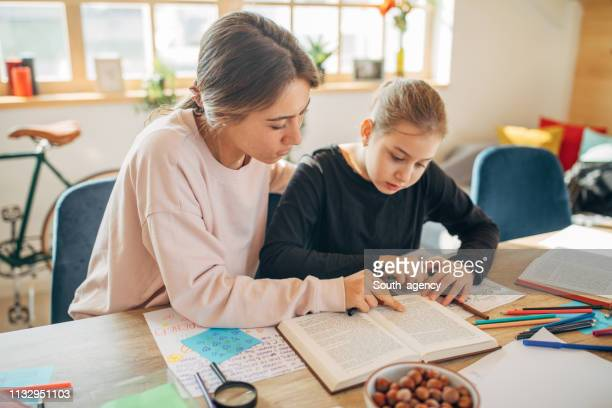 private teacher helping girl doing homework - tutor stock pictures, royalty-free photos & images