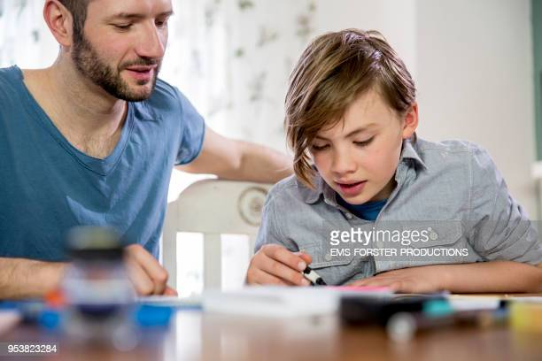 private tutoring lesson for 10 years old blonde elementary school boy while doing his homework together with male tutor in his thirties. - 10 11 years stock pictures, royalty-free photos & images