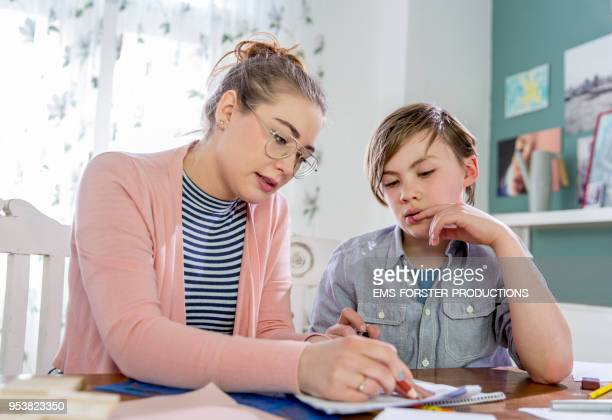 private tutoring lesson for 10 years old blonde primary school boy while doing his homework together with female tutor in her twenties. - instrutor - fotografias e filmes do acervo