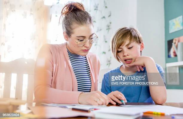 Private tutoring lesson for 10 years old blonde primary school boy while doing his homework together with female tutor in her twenties.
