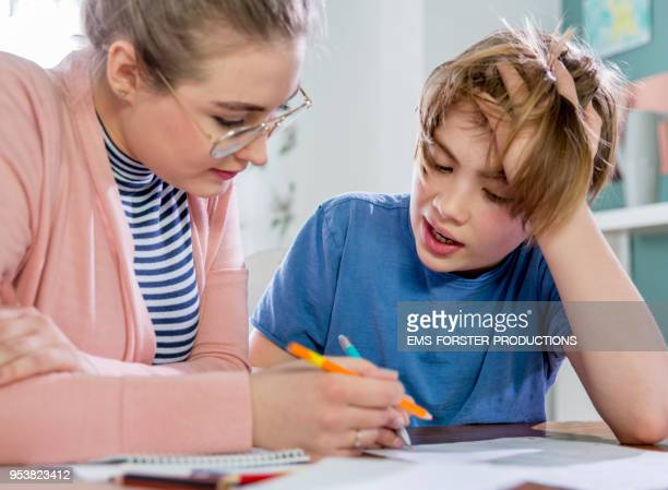 private tutoring lesson for 10 years old blonde primary school boy while doing his homework together with female tutor in her twenties. - 10 11 years stock pictures, royalty-free photos & images