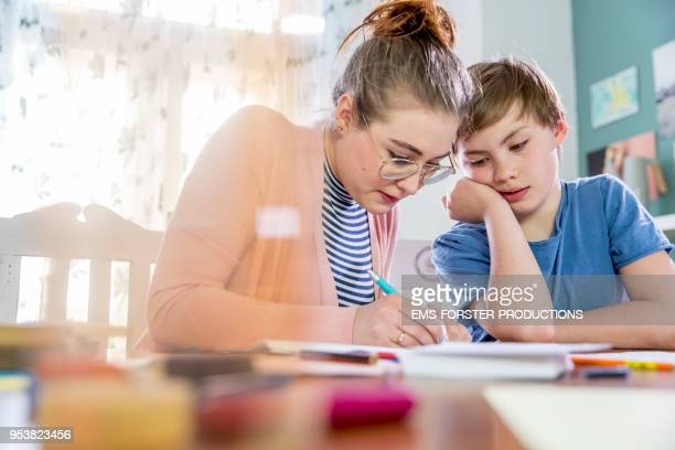 private tutoring lesson for 10 years old blonde primary school boy while doing his homework together with female tutor in her twenties. - 25 29 years stock pictures, royalty-free photos & images