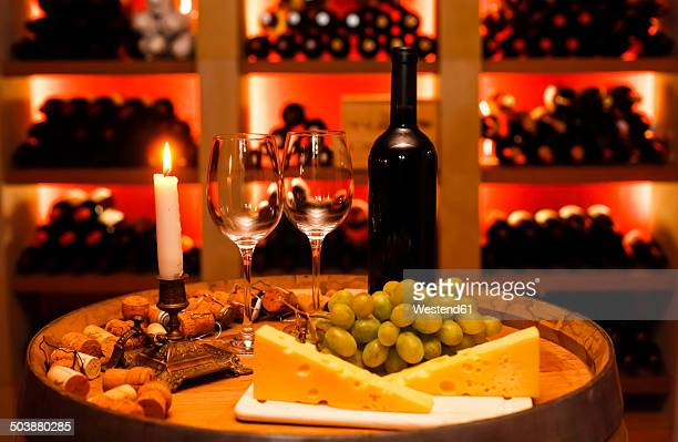 private wine cellar with bottle of red wine, two wine glasses, grapes, cheese and lighted candle in foreground - things that go together stock pictures, royalty-free photos & images