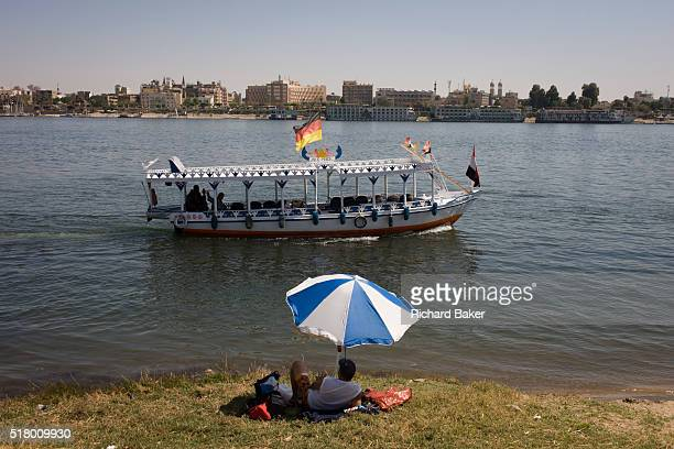 Privately-owned motorboat ferry flying the German flag and dependent on all tourist trade crosses the River Nile in front of a sunbather at Luxor,...