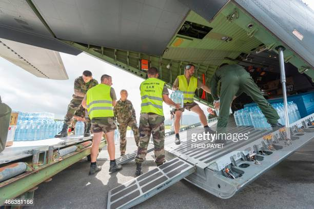 Privates load water bottles into a French Army logistical transport plane bound for Vanuatu transporting food water and relief at the Aerial Military...