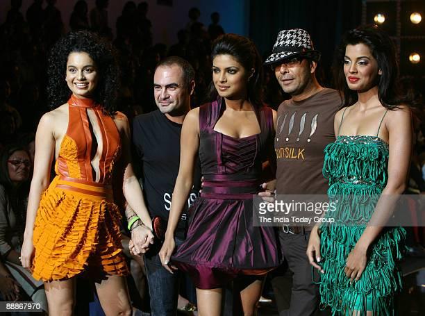 Priyanka Chopra along with Mugdha Godse Kangna Ranaut Fashion Designer Narendra Kumar and hair stylist Andrew Barton are walking on the ramp with...