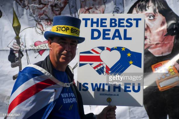 Pro and Anti Brexit demonstrators are seen waving flags and displaying placards outside the Houses of Parliament London on May 15 2019 Mrs May has...
