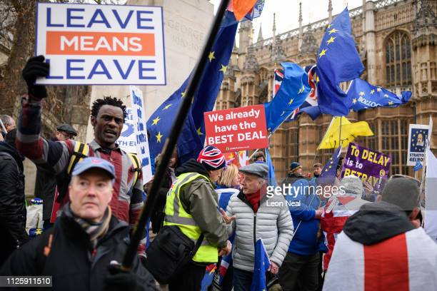 Pro and anti Brexit protestors discuss the vote and ongoing political processes as they demonstrate near to the Houses of Parliament on January 29...