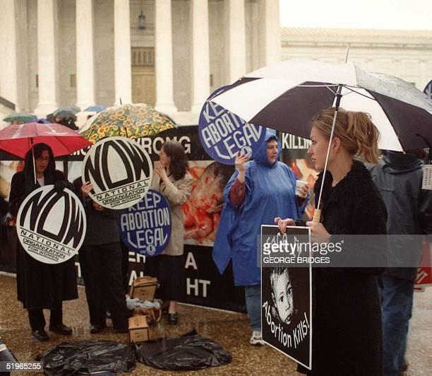 Pro and antiabortion protesters march 25 April 2000 in front of the US Supreme Court Building in Washington DC After an eightyear absence justices...