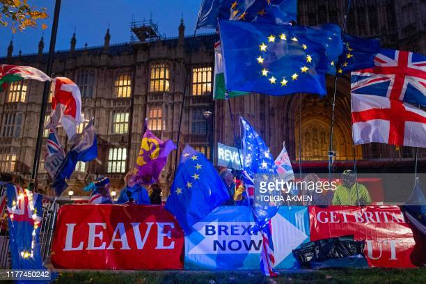 TOPSHOT Pro and antiBrexit protesters wave flags and hold banners as they demonstrate outside of the Houses of Parliament in central London on...
