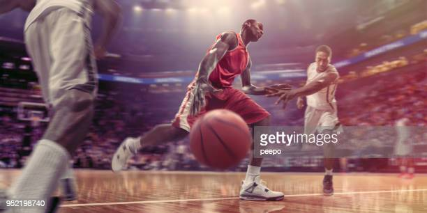 pro basketball player dribbling ball past opponents during basketball game - basketball stadium stock pictures, royalty-free photos & images