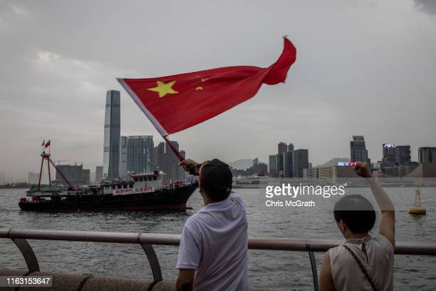 Pro Beijing demonstrators wave the Chinese national flag at a ship during a rally in front of the Legislative Council Complex to show their support...